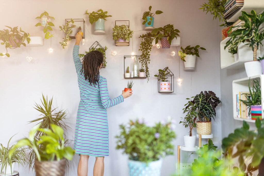 eune femme prenant soin de ses plantes d'intérieur à la maison